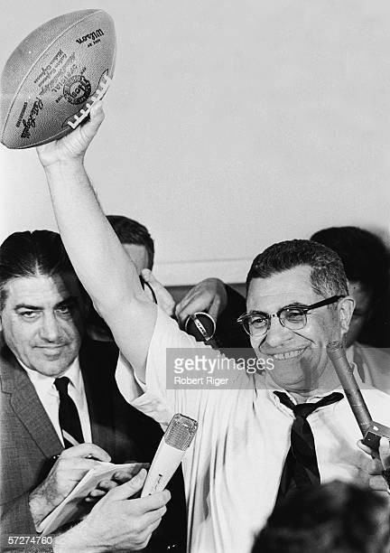 American professional football coach Vince Lombardi head coach for the Green Bay Packers holds a football over his head and grins as he is...