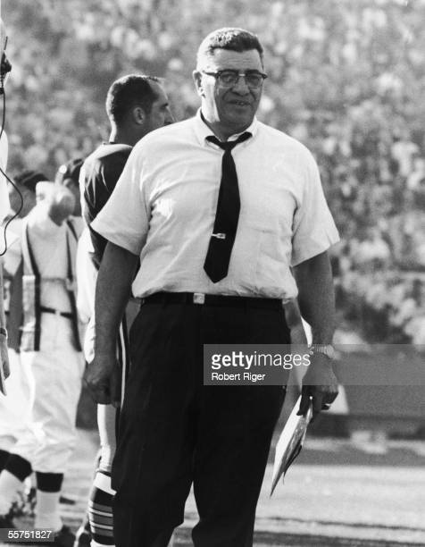 American professional football coach Vince Lombardi holds a clipboard and stands on the sidelines near player Zeke Bratkowski quarterback for the...