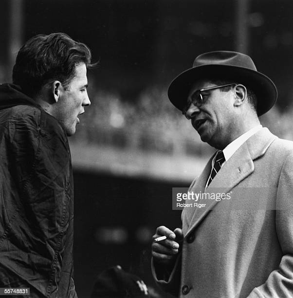 American professional football coach Vince Lombardi holds a lit cigarette and talks to professional football player Frank Gifford of the New York...