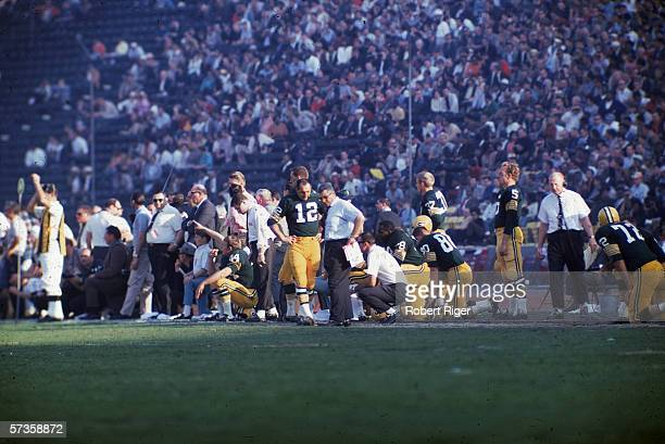 American professional football coach Vince Lombardi talks to Green Bay Packers quarterback Zeke Bratkowski as they and other Packers players and...