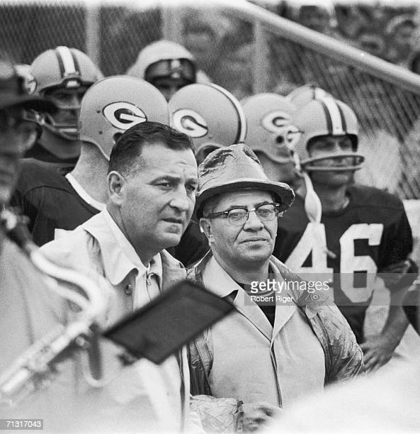 American professional football coach Vince Lombardi watches a game from the sidelines with an assistant and some players late 1950s or 1960s Lombardi...
