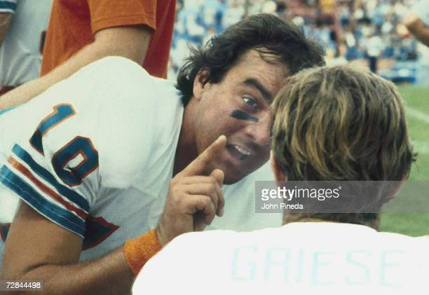American professional football player and later coach Don Strock backup quarterback of the Miami Dolphins helps colleague starting QB Bob Griese with...