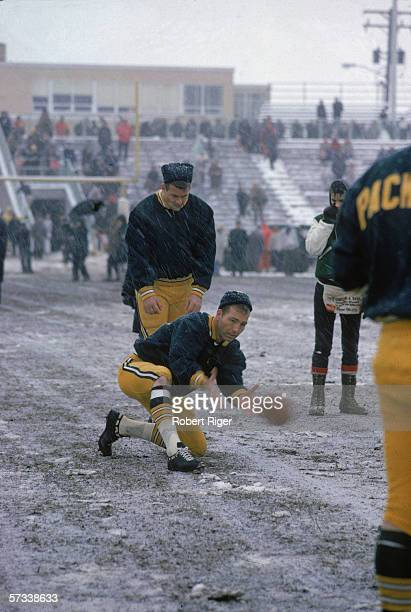 American professional football player Bart Starr quarterback for the Green Bay Packers practices with a kicker in the snow before a game against the...