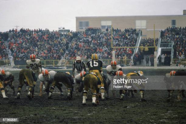 American professional football player Bart Starr quarterback of the Green Bay Packers calls a play on a very muddy Lambeau Field during the NFL...