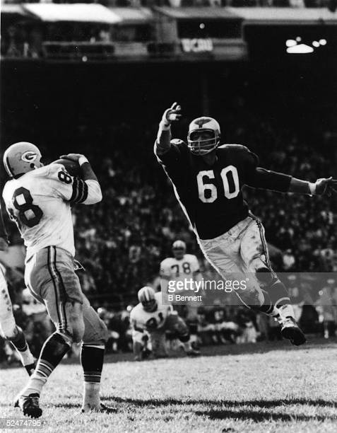 American professional football player Chuck Bednarik a twoway player for the Philadelphia Eagles leaps toward an unidentified player from the Green...