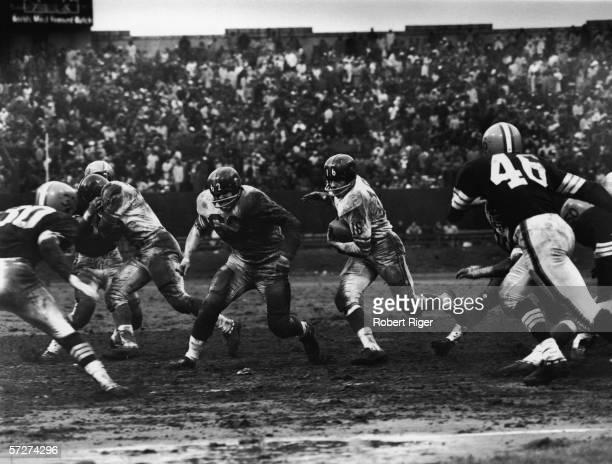 American professional football player Frank Gifford running back for the New York Giants runs as he carries the ball during a game with the Cleveland...