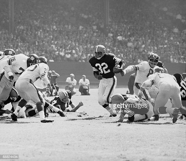 American professional football player Jim Brown of the Cleveland Browns runs with the ball towards the defensive line of the New York Giants...