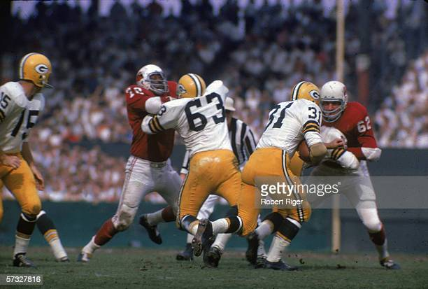 American professional football player Jim Taylor of the Green Bay Packers takes the handoff from quarterback Bart Starr and runs as his teammates...