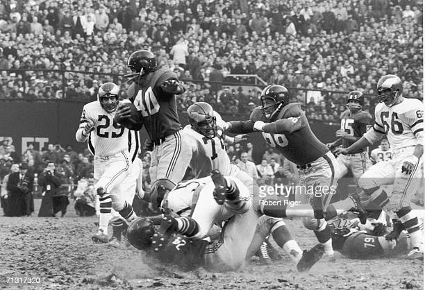 American professional football player Joe Morrison of the New York Giants rushes through the Philadelphia Eagles as teammates Jack Stroud Phil King...