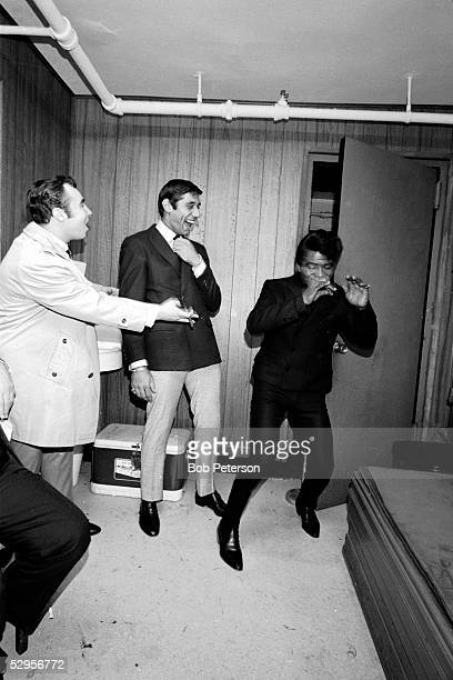American professional football player Joe Namath laughs as rhythm and blues soul and funk musician James Brown demonstrates dance moves 1966