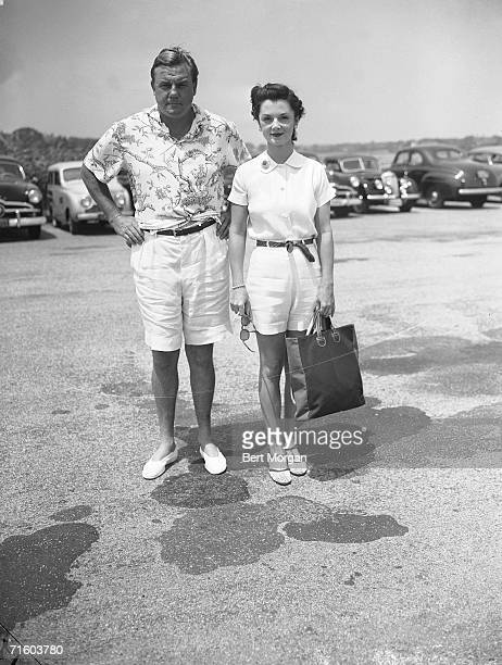 American professional football player John Sims Kelly and his wife debutante Brenda Frazier pose for a photograph in a parking lot as they wear their...