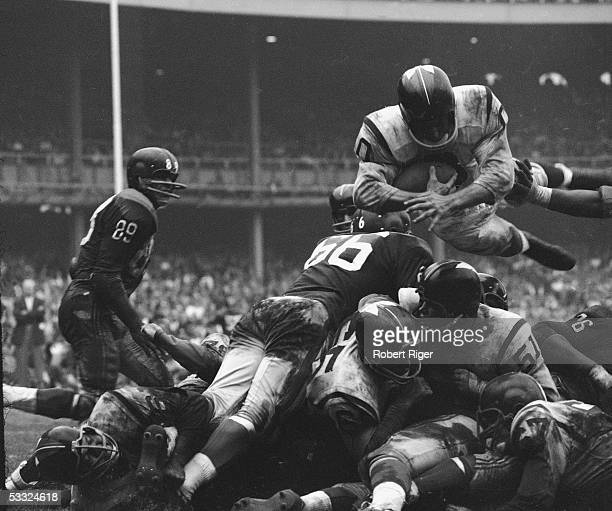 American professional football player Johnny Olszewski of the Washington Redskins leaps with the ball over a pile of New York defensemen and his own...