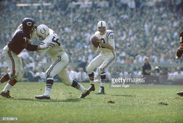 American professional football player Johnny Unitas of the Baltimore Colts prepares to pass as his opponents close in during a game against the...