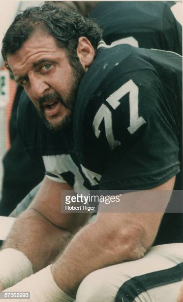 American professional football player Lyle Alzado of the Los Angeles Raiders sits on the bench during a game early 1980s