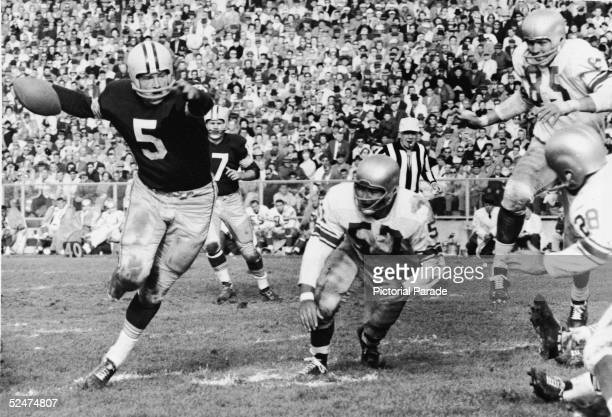 American professional football player Paul Hornung halfback for the Green Bay Packers carries the ball through a hole in the defense during a game...