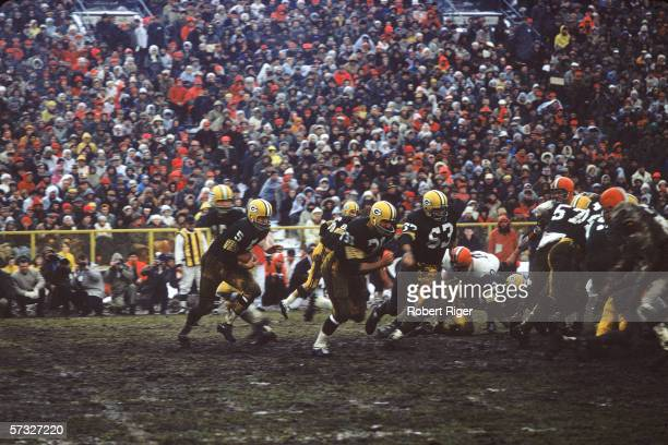American professional football player Paul Hornung of the Green Bay Packers takes the ball in a hand off from quarterback Bart Starr and follows Jim...