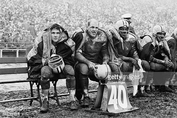 American professional football player Ray Nitschke of the Green Bay Packers sits on the bench with teammates during an away game against the 49ers...