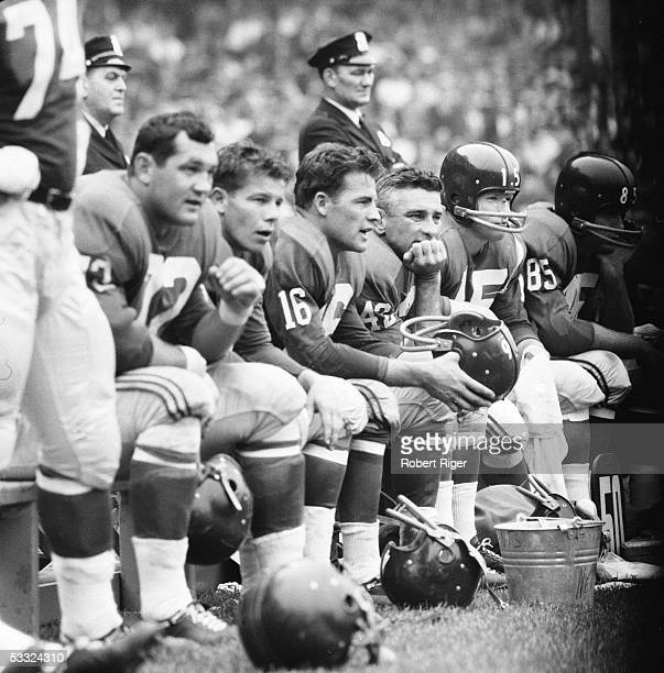 American professional football players Kyle Rote , Frank Gifford, and Charlie Conerly , sit together on the bench during a game, Yankee Stadium, New...