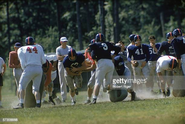 American professional football players of the New York Giants run and carry the ball and practice blocking as they attend training camp before the...