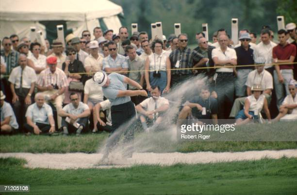 American professional golfer Jack Nicklaus hits the ball from in a sand trap before a crowd of respectful spectators some of whom watch through...