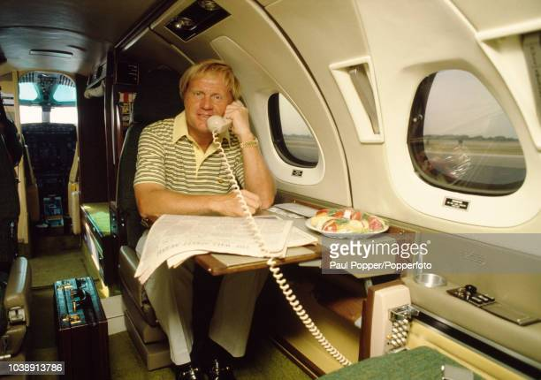 American professional golfer Jack Nicklaus pictured taking a telephone call aboad his private jet in June 1983. A copy of the Wall Street Journal...
