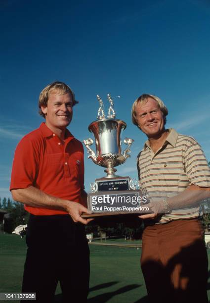 American professional golfers Johnny Miller and Jack Nicklaus lift the winners trophy after finishing in first place to win the 1983 Chrysler Team...