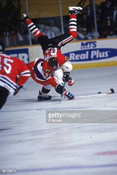American professional hockey player Jeremy Roenick center for the Chicago Blackhawks stumbles over American professional hockey player Keith Tkachuk...