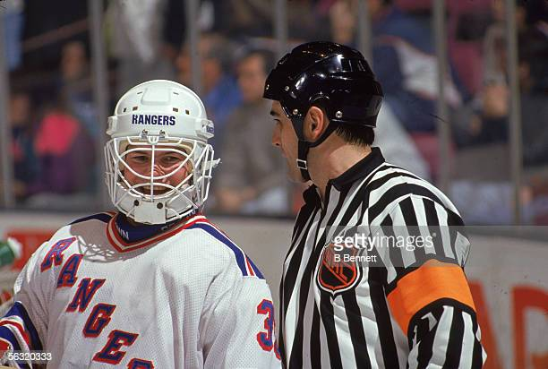 American professional hockey player Mike Richter, goalie for the New York Rangers, shares a laugh with referee Andy Van Hellemond during a home game...