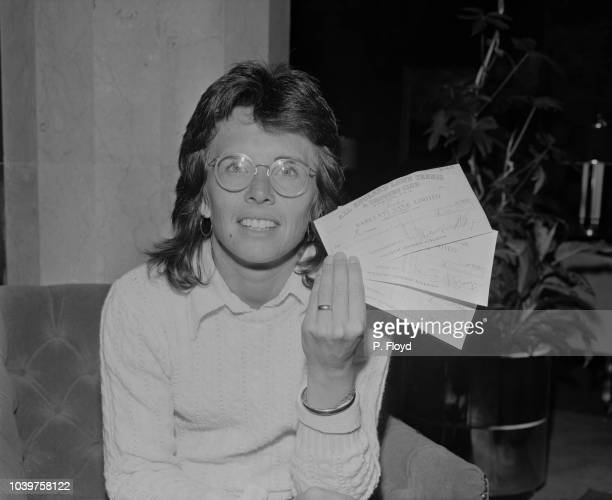 American professional tennis player Billie Jean King pictured holding three cheques, sent to her by the All England Lawn Tennis and Croquet Club, in...