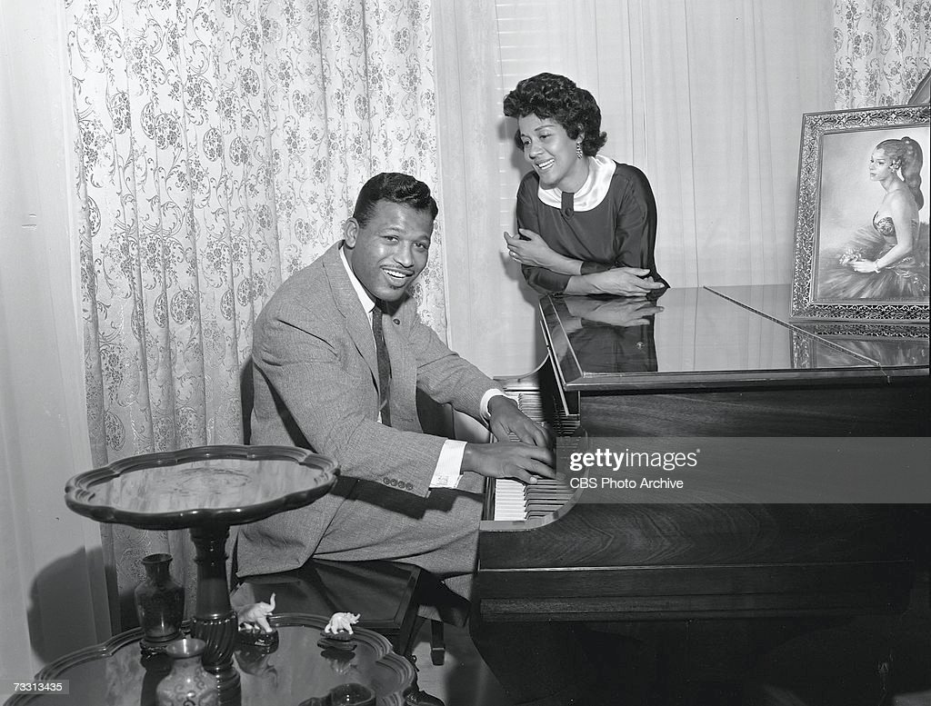 American professional welterweight and middleweight boxing champion of the world Sugar Ray Robinson (1921 - 1989) poses at home for the CBS celebrity interview program 'Person to Person' as he sits at a grand piano and his wife Edna Mae leans on the top and looks on, October 26, 1957.