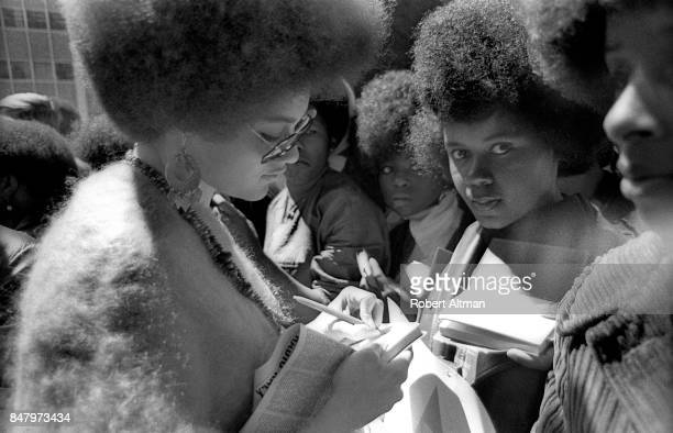 American professor of law and part of the Black Panther Party Kathleen Neal Cleaver signs autographs for a few girls during a Free Huey Rally in...