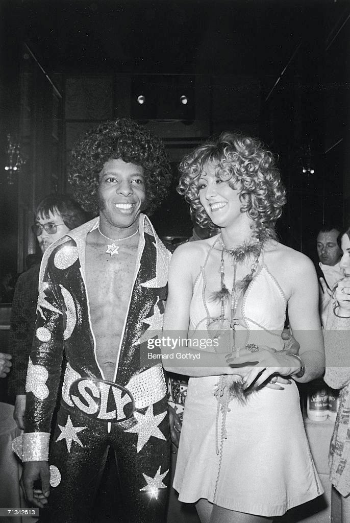 American psychedelic musician Sly Stone (left) wears an outrageous jumpsuit, at Madison Square Garden, New York City, 25th March 1974.