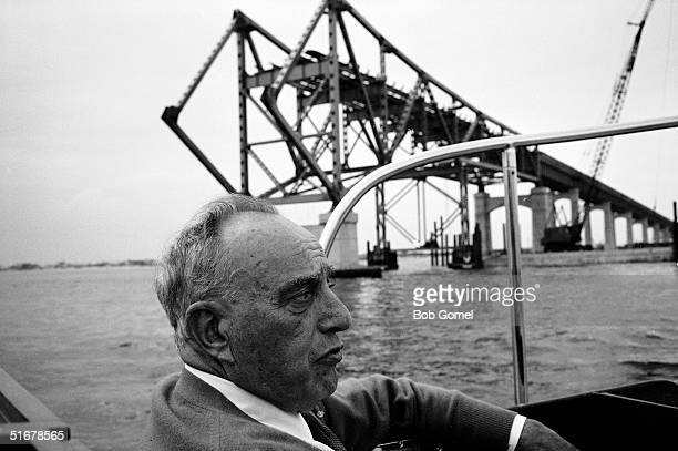 American public official and city planner Robert Moses rides in a boat past the construction of a Long Island highway bridge probably the Captree...