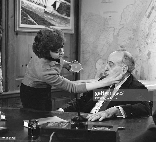 American public official and city planner Robert Moses sits as his desk as a woman touches up his makeup prior to an interview for the CBS Reports...
