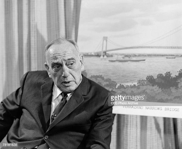 American public official and city planner Robert Moses sits next to an illustration of the Verrazano Narrows Bridge during an interview for the 'Eye...