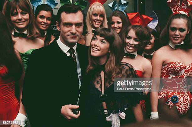 American publisher and club owner Hugh Hefner pictured with his girlfriend Barbi Benton and various bunny girls during a visit to his London Playboy...