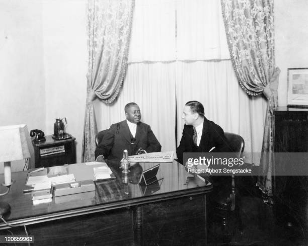 American publishers Robert Sengstacke Abbott and William B. Ziff talk together over cigars, 1929.