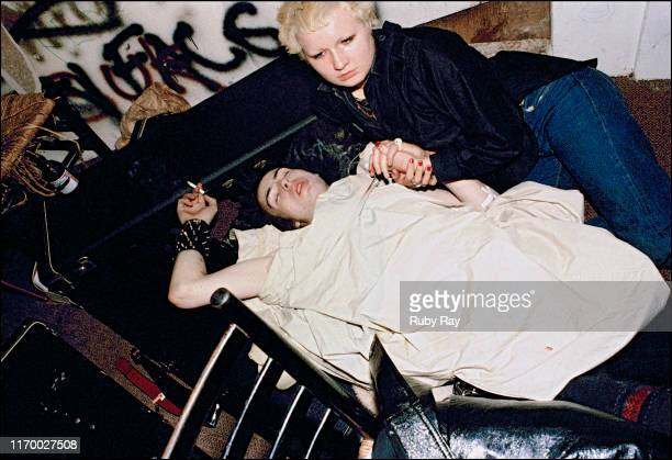 Sex Pistol Sid Vicious and Hellin Killer of the LA girl gang the Plungers rest on the floor backstage after Sid overdid it cutting himself onstage at...