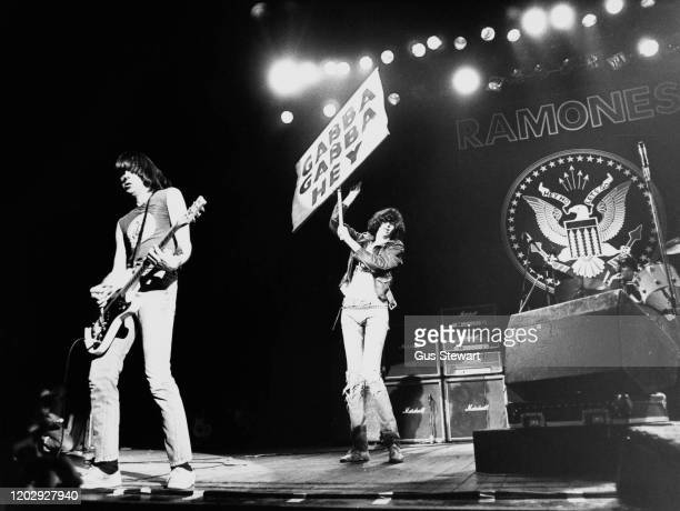 American punk rock band The Ramones on stage, UK, 1978; they are Johnny Ramones and Joey Ramone , who is holding a sign which says 'Gabba Gabba Hey'.
