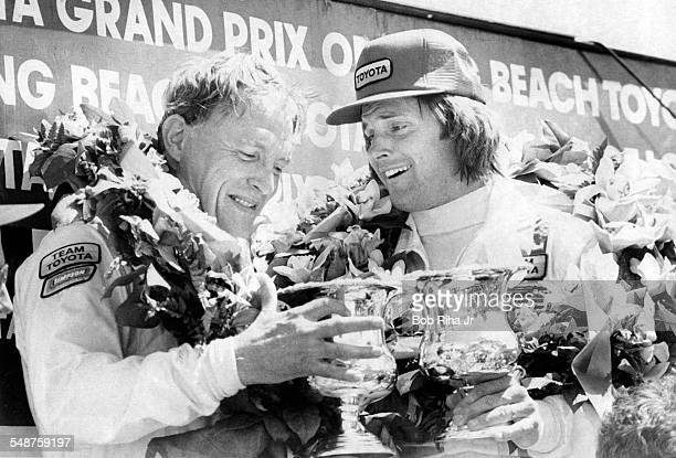 American race car driver Dan Gurney and former professional athlete Bruce Jenner pose together in the Winner's Circle with at the 1982 Toyota...