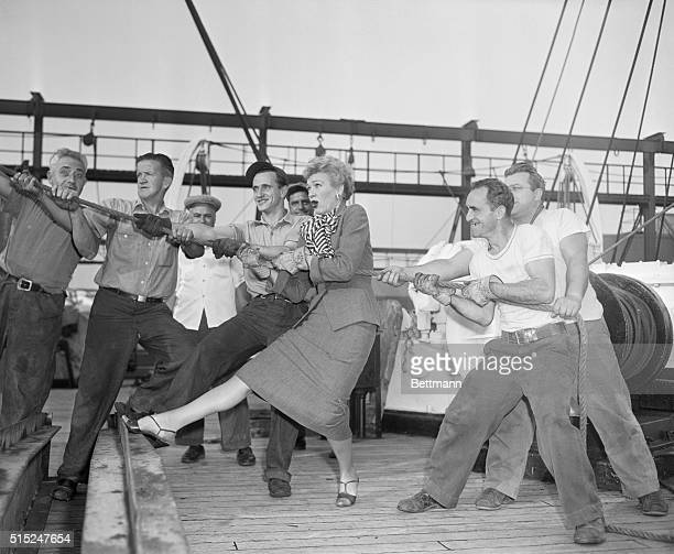 American radio and television actress Eve Arden helps longshoremen aboard the Ile de France as they pull into port