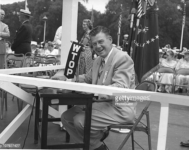 American radio broadcaster Arthur Godfrey smiles as he broadcasts the ceremony the marks the 100th anniversary of the laying of the Washington...