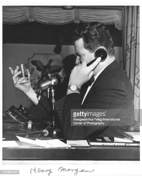 American radio host and comedian Henry Morgan talks on the phone a shot glass in one hand as he broadcasts into a WMGM microphone New York New York...