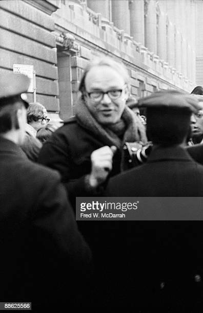 American radio journalist Bob Fass holds a camera as he looks over the shoulders of police officers at a draft protest at the Whitehall Army...