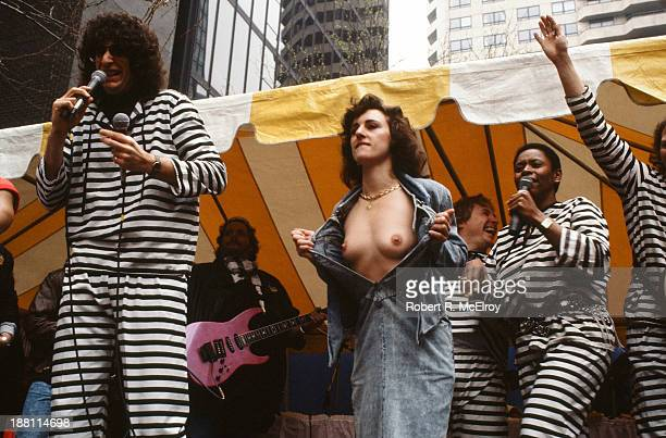 American radio show personalities Howard Stern and Robin Quivers stand with microphones as an unidentified woman in denim bares her breasts at Howard...