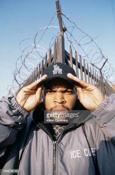 American rapper and actor Ice Cube posing in front of a spiked fence topped with barbed wire USA circa 1992