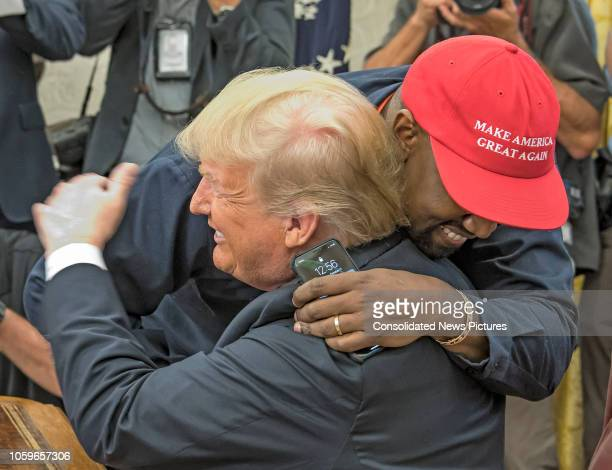American rapper and producer Kanye West embraces real estate developer and US President Donald Trump in the White House's Oval Office Washington DC...