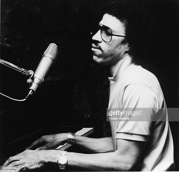 American r&b and pop singer Lionel Richie, wearing a t-shirt and sunglasses, plays a piano with his eyes closed, early 1980s.