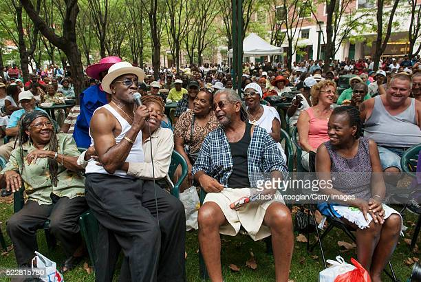 American RB and Soul musician Billy Paul sits on an audience member's lap as he performs during the Brooklyn Academy of Music's Rhythm Blues Festival...