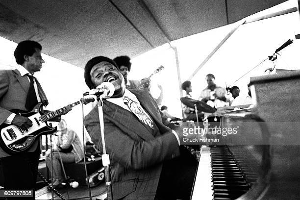 American R&B musician Fats Domino plays piano as he performs onstage during the New Orleans Jazz & Heritage Festival at the Fair Grounds Race Course,...